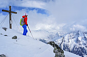 Woman back-country skiing standing on summit of Grundschartner, Grundschartner, Zillergrund, Zillertal Alps, Tyrol, Austria