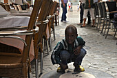 Black boy, child of a street vendor, between chairs of street bars at de Don Juan Diaz, near the Cathedral, Malaga, Andalusia, Spain, Europe