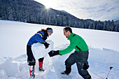 Two persons building igloo, Chiemgau range, Chiemgau, Upper Bavaria, Bavaria, Germany