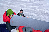 Two persons sitting in igloo and preparing air mattress, Chiemgau range, Chiemgau, Upper Bavaria, Bavaria, Germany