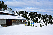 Three persons back-country skiing in front of Neue Bamberger Huette, Kurzer Grund, Kitzbuehel range, Tyrol, Austria