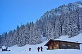 Three persons back-country skiing ascending past alpine hut towards Sonntagshorn, Sonntagshorn, Chiemgau range, Salzburg, Austria