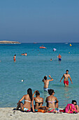 White sandy beach with three women sitting on the beach and men playing volleyball in the water, Nissi Beach near Ayia Napa northeast of Larnaca, Larnaca District, Cyprus
