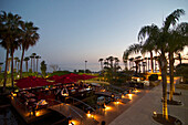 Garden restaurant with palm trees and sea after sunset in the Le Meridien Hotel, Limassol, Limassol District, Cyprus
