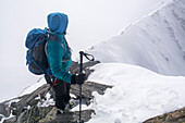 A female alpinist in skitouring equipment standing on an exposed ridge in combined terrain while looking down to her tracks at the beginning of the ridge, Wasenhorn or Punta Terrarossa, Simplon Region, Lepontine Alps, canton of Valais, Switzerland