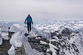 A female mountaineer walking on an exposed ridge, south ridge of Monte Leone, Lepontine Alps, canton of Valais and region of Piedmont, national border of Switzerland and Italy