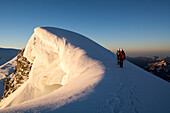 A male and a female alpinist on the summit ridge of Roccia Nera, one of the five summits of the Breithorn massif, next to them big cornices, Valais Alps, canton of Valais and region of Aosta Valley, national border of Switzerland and Italy