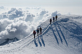 Two rope teams, each of three alpinists, walking across the airy snow crest at the end of the south ridge of Weissmies, Pennine Alps, canton of Valais, Switzerland