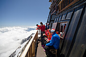 Alpinists in front of the Margherita Hut on the summit of the 4554 meter high Signalkuppe or Punta Gnifetti, highest hut in the Alps, below them a sea of clouds over northern Italy, Monte Rosa massif, Pennine Alps, Italy