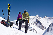 A female and a male mountaineer with their touring skis next to them, standing on the summit of Roccia Nera, Breithorn massif, behind them the summit of the Dufourspitze, Monte Rosa massif, Pennine Alps, canton of Valais and region of Aosta Valley, nation