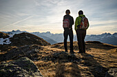 Two women in hiking gear standing on an alpine meadow near the alp of Fessis and looking towards the summits of the Glarus Alps, canton of Glarus, Switzerland