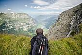 Eine junge Frau liegt auf dem Bauch kurz vor dem Gipfel des Vorder Glärnisch und blickt über den Abgrund hinab zu den Dörfern Netstal, Mollis und Näfels, Glarner Alpen, Kanton Glarus, Schweiz