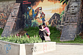A young couple kissing in front of a street painting by the artist Jorge Alcoreza, a boy is watching them, La Paz, Bolivia