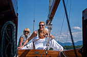 Two young women on a sailing boat, Chiemsee, Bavaria, Germany