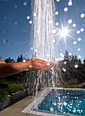 Hands under an outdoor shower, Ehrwald, Tyrol, Austria
