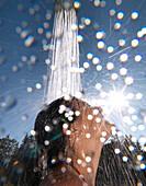 Young woman under an outdoor shower, Ehrwald, Tyrol, Austria