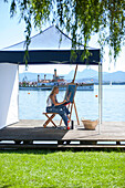 Young Woman with artist's easel painting, Fraueninsel, Chiemsee, Bavaria, Germany