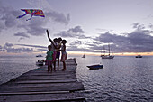 Children playing with a kite on a jetty in sunset, Dominica, Lesser Antilles, Caribbean
