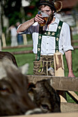 Man wearing traditional clothes drinking a glass of beer, Viehscheid, Allgau, Bavaria, Germany