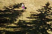 Junge Frau wandert einen Berg hinauf an einem sonnigen Tag, Oberstdorf, Bayern, Deutschland