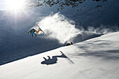 Young male skier doing a backflip over a rock, Pitztal, Tyrol, Austria