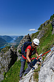Woman climbing the Via ferrata del Centenario in front of Lake Lugano and the highest Swiss mountain, the snow-capped Dufourspitze (4634 m) in the Monte Rosa massif, Italy and Switzerland