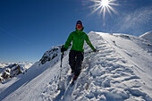 A mountaineer descending over the northern ridge of Piz Sarsura (3178 m), Grisons, Switzerland, Europe