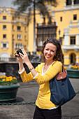 Cheerful woman with camera on Plaza de Armas square, Lima, Lima, Peru