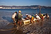 Fishermen unload catch from fishing boat on Playa Las Hamacas beach, Acapulco, Guerrero, Mexico