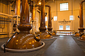 Giant copper pot stills in the Still Room at The Glenmorangie Whisky Distillery, Tain, Ross-shire, Highland, Scotland, United Kingdom
