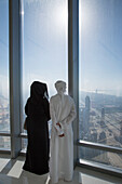 Arab man and woman in traditional clothing enjoy the view from At The Top observation deck on level 124 of Burj Khalifa tower, Dubai, Dubai, United Arab Emirates