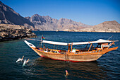 People jump from boat into water during traditional dhow boat excursion to Telegraph Island in fjord of Musandam Peninsula, near Khasab, Musandam, Oman