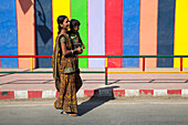Young woman with child in front of colorful wall with lamp shadow, Diu Island, Daman and Diu, India