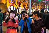 Teenage girls take photographs with smartphones at Nanjing Road pedestrian zone, Shanghai, China