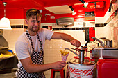 Man pours mayonnaise on fries at Pommes Frites shop, Amsterdam, North Holland, Netherlands