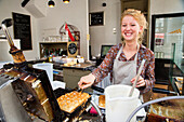 Cheerful Gaufre waffle baker at Queen of Waffles bakery, cafe and shop, Antwerp, Flemish Region, Belgium