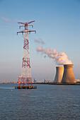 Power line mast tower and Doel Nuclear Power Station alongside Scheldt river at sunset, near Antwerp, Flemish Region, Belgium