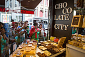 People admire chocolates for sale through store window at Chocolate City candy shop, Bruges (Brugge), Flemish Region, Belgium