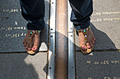 Woman with sandals stands on Prime Meridian line at the Royal Observatory, Greenwich, London, England, United Kingdom