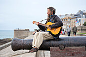 Street musician sits on cannon on city wall fortress, Saint-Malo, Brittany, France