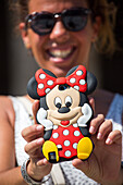 Woman smiles as she holds Minnie Mouse smartphone cover, Santiago de Compostela, Galicia, Spain