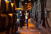 Man and woman enjoy port wine tasting in cellar of Burmester winery, Vila Nova de Gaia, Porto, Norte, Portugal