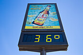 36 degrees celsius on temperature sign with beer advertisement, Seville, Andalusia, Spain