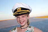 Young girl with captain's hat aboard cruise ship MS Deutschland (Reederei Peter Deilmann) [MR], near Seville, Andalusia, Spain