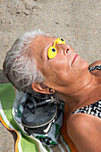 Elderly woman with sun protection over eyes on Caleta Playa beach, Malaga, Costa del Sol, Andalusia, Spain
