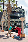 Clown Street performer shakes hands with man with replica of historic sailing ship Santisima Trinidad in port behind, Alicante, Andalusia, Spain