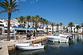 Fishing boats in harbor with bars and restaurants behind, Fornells, Menorca, Balearic Islands, Spain