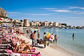 People relax at Mondello beach on a sunny Sunday morning as beach toy vendor strolls by, Mondello, near Palermo, Sicily, Italy