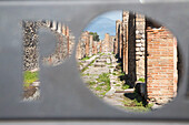 The ruins of ancient Pompeii seen through information sign, Pompeii, Campania, Italy