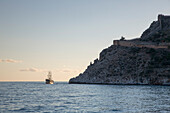 Excursion sailing boat in bay and Alanya Castle fortification at sunset, Alanya, Antalya, Turkey